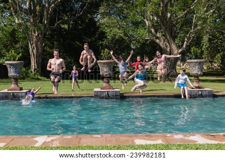 Boys Girls Jump Swim Pool Teen boys girl running jumping into swimming pool water home summer playtime - stock photo