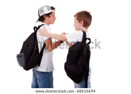 boys going to school, greeting one another, seen from the back, on white, studio shot - stock photo