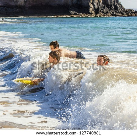 boys have fun riding in the waves - stock photo