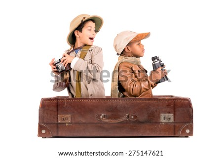Boys in costume playing African game drive inside an old suitcase - stock photo