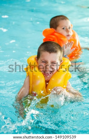 Boys in life jacket learning to swim in the swimming pool  - stock photo