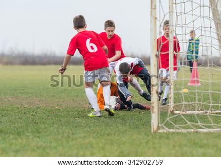 boys kicking football on the sports field - stock photo
