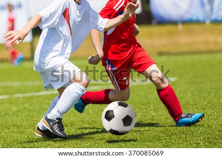 Boys Kicking Football on the Sports Field. Football match for children. Training and football soccer tournament - stock photo