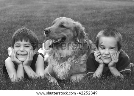 Boys Laying in the grass with Dog - stock photo