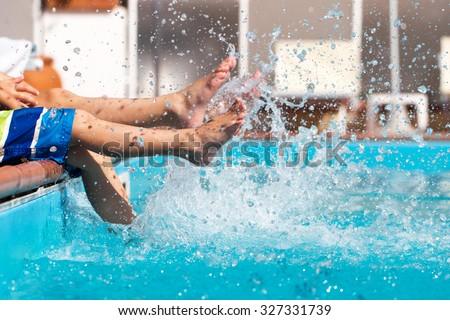Boys legs splashing water in pool, summer holiday - stock photo