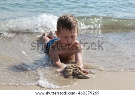 Boys lying on the sand on a sea beach. He is playing with sand