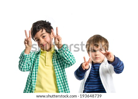 Boys making victory sign over white background