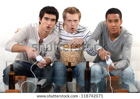 Boys night in with computer games, beer and popcorn - stock photo
