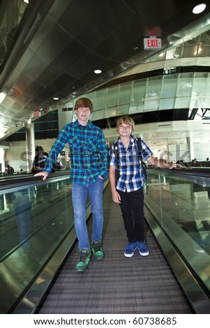 boys on a moving staircase in the airport, ready for flying home - stock photo