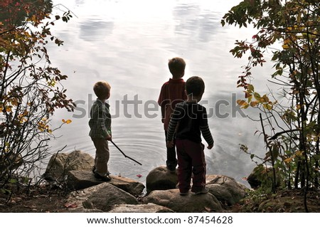 Boys on the shore of Walden Pond watch the cloud reflection in the water - stock photo