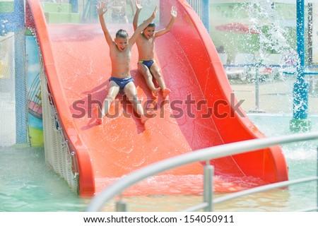 boys on water toboggan at aqua-park.Summer holiday.  - stock photo