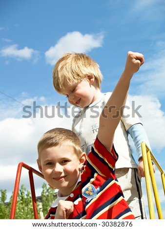 Boys play on a children's playground in the spring