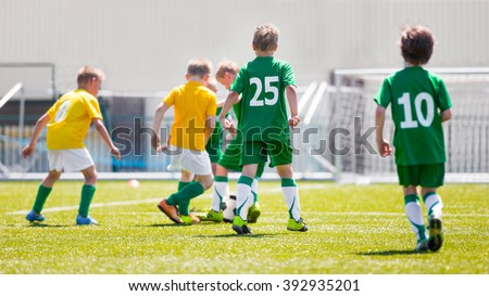 Boys play soccer match. Yellow and green team on a sports field - stock photo