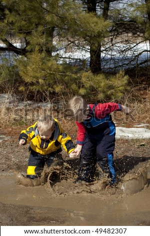 Boys Playing and Splashing in a Mud Puddle - stock photo
