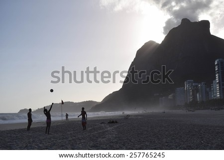 Boys playing at Rio's beach at stunning sunset - stock photo