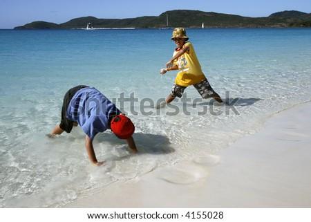 Boys playing at Whitehaven Beach - stock photo