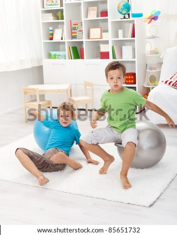 Boys playing dangerous games - jumping on large balls and falling