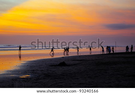 Boys playing football on beach at sunset, Seminyak, Bali, Indonesia .