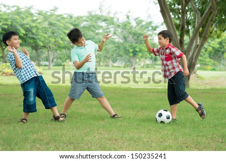 Boys playing football on the park lawn - stock photo