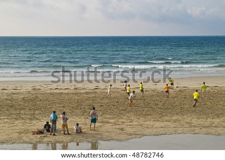 Boys playing football with low tide - stock photo