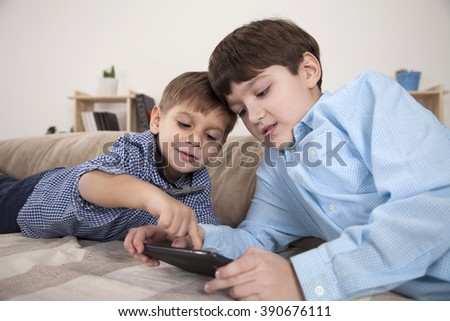 Boys playing on tablet computer in the living room