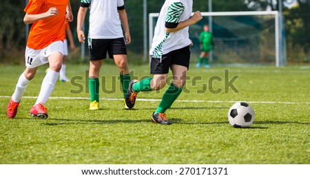 Boys playing soccer football match. Players footballers running and playing football match - stock photo