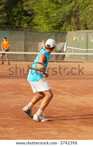 boys playing tennis on the open court - stock photo