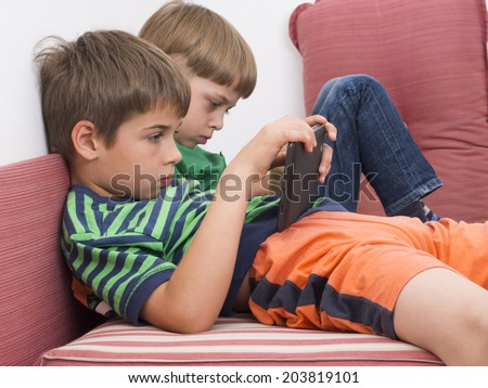 boys playing video games on the tablet computers - stock photo