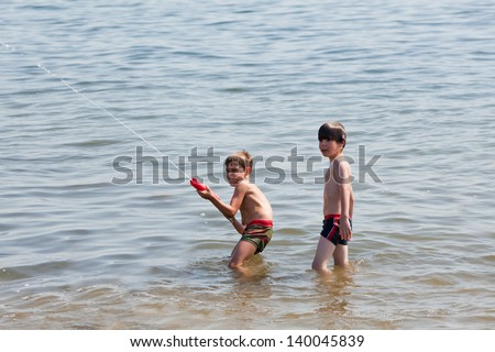Boys playing with water gun - stock photo