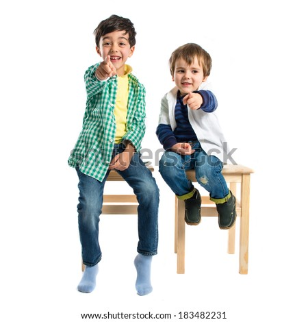 Boys pointing to the front over grey background