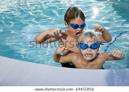 Boys pretending to be tough, playing in swimming pool, 7 and 9 years - stock photo