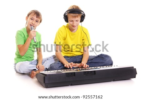 Boys rehearse on a synthesizer on a white background - stock photo