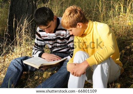 boys sit in autumn forest with a book - stock photo