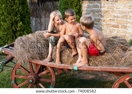boys sitting on a hay bale - stock photo