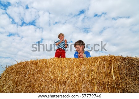 boys sitting on a large hay bale on sky background - stock photo