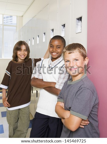 Boys smiling and leaning on school lockers - stock photo