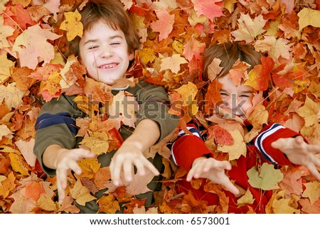 Boys Throwing Fall Leaves - stock photo