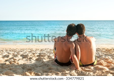 Boys together in the beach looking at the sea - stock photo