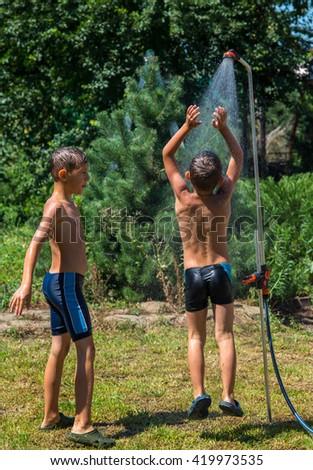 Boys under a shower in the garden - stock photo