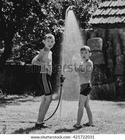 Boys under a shower in the garden in hot day - stock photo
