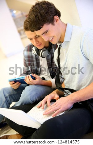 Boys using laptop computer in school building