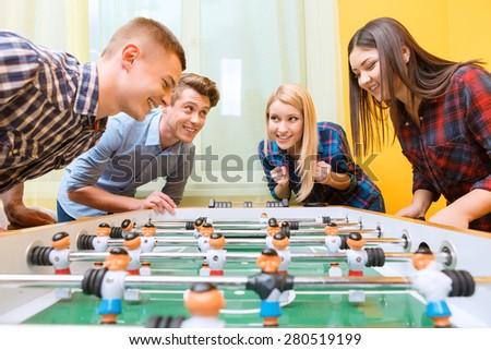 Boys vs girls. Young smiling boy playing air hockey against young Asian girl watching the play while their friends standing near and cheering them up - stock photo
