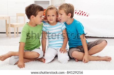Boys whispering to a girl childish secrets - indoors scene - stock photo