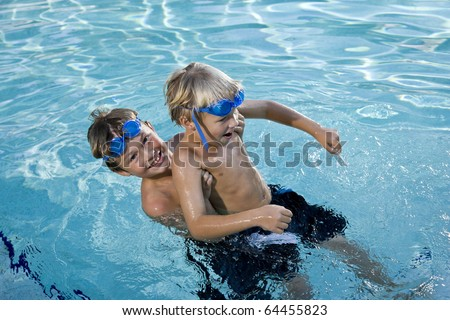 Boys will be boys - playing on side of swimming pool, 7 and 9 years - stock photo