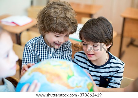 Boys with a globe in classroom - stock photo
