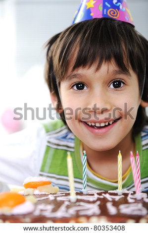 Boys with candles on cake, happy birthday party - stock photo
