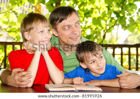 boys with their dad reading a book