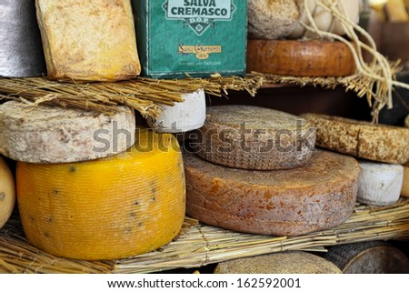 BRA - SEPTEMBER 22: Different types of mature hard cheese on the stand. Hard cheese produced by stirring and draining a mixture of curd and whey  in Bra, Italy on September 22, 2013. - stock photo