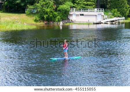 Bracebridge, Ontario - July 17, 2016: An unidentified paddler is propelling her paddling board on Muskoka River in Bracebridge in front of a boathouse.