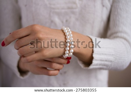 Bracelet of pearls on a female hand. Slender girl dressed in a white sweater, she wears a pearl bracelet on her right arm.